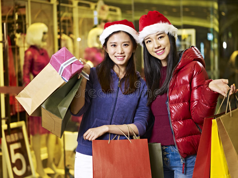 Two young asian women shopping for christmas royalty free stock photo