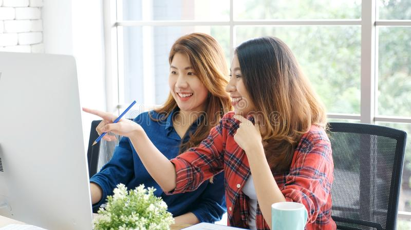 Two young asian women working with computer at home office with happy emotion, working at home, small business, office casual royalty free stock image