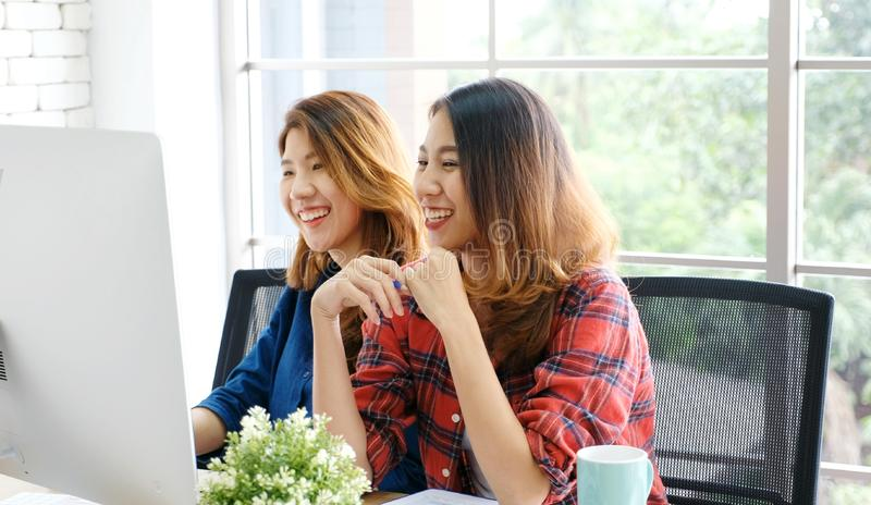 Two young asian women working with computer at home office with happy emotion, working at home, small business, office casual. Lifestyle, adult learning online stock image