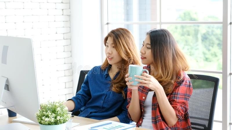 Two young asian women working with computer at home office with happy emotion, working at home, small business, office casual stock images