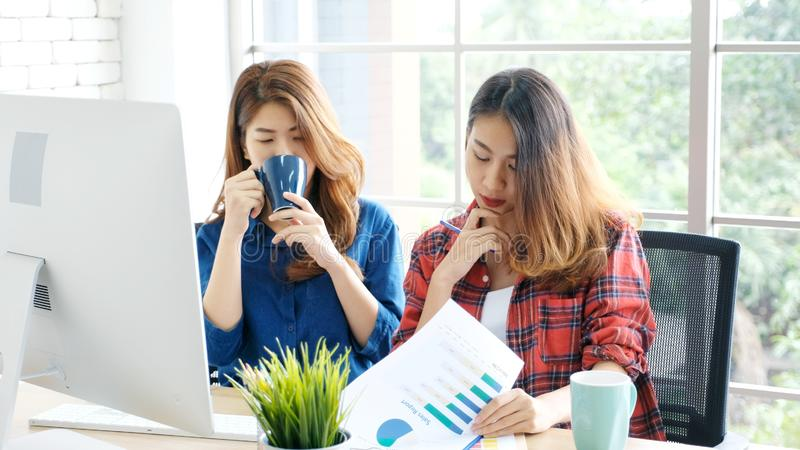 Two young asian women working  at home office with happy emotion moment, working at home, small business, office casual lifestyle. Two young asian women working stock photography