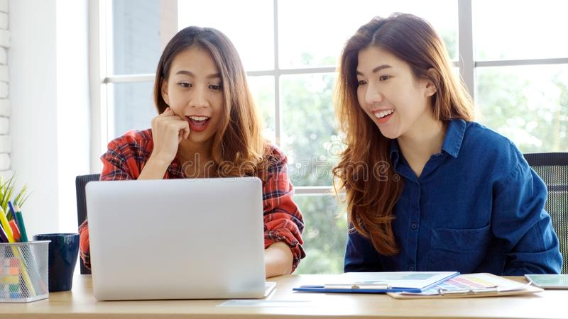 Two young asian women working with laptop computer at home office with happy emotion moment, working at home, small business, stock images