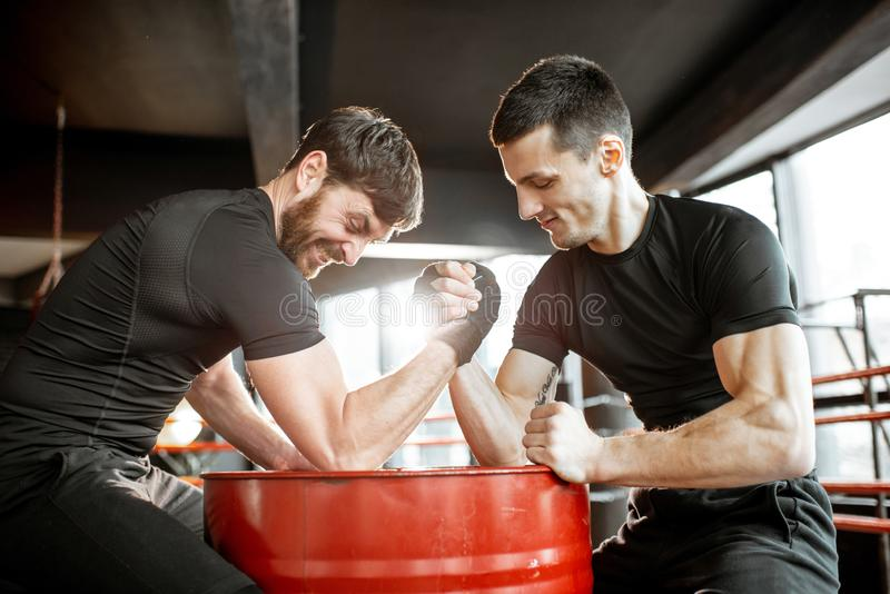 Men having arm wrestling in the gym. Two young athletes in black sportswear having a hard arm wrestling competition on a red barrel in the gym royalty free stock image