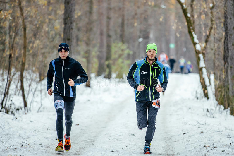 Two young athletes runners running in snow trail woods. Ekaterinburg, Russia - November 26, 2016: two young athletes runners running in snow trail woods during stock photos