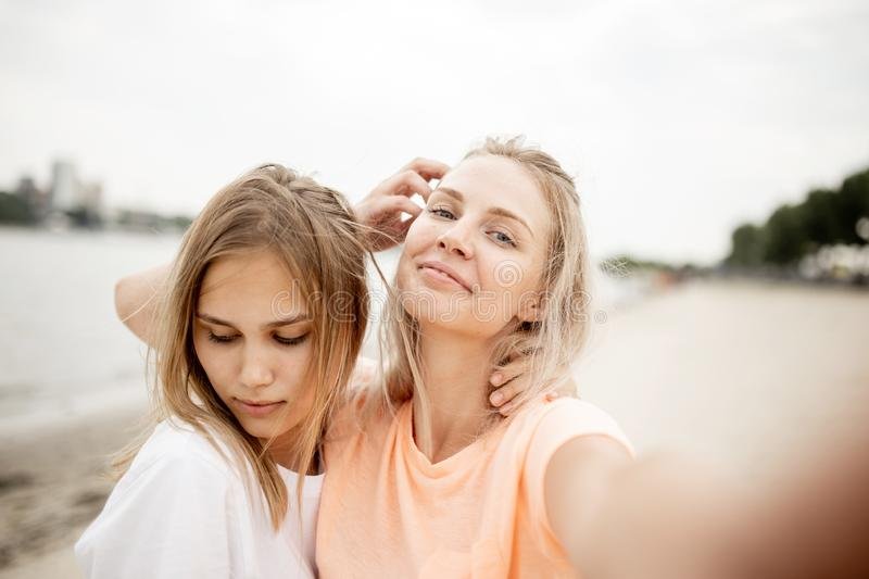 Two young attractive blonde girls take a selfie on the beach on a warm windy day stock photos