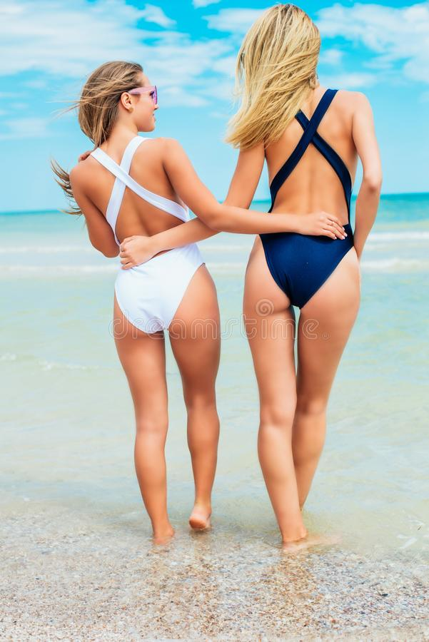 Two young attractive girls with long hair in a swimsuits relax on beach in the sea. In sunny hot day royalty free stock images