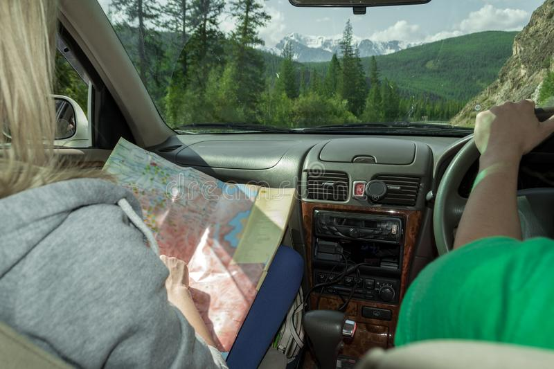Two young attractive girls travel by car among the mountains covered with green trees, the blonde in the passenger seat points th. E way looking at the map stock photography