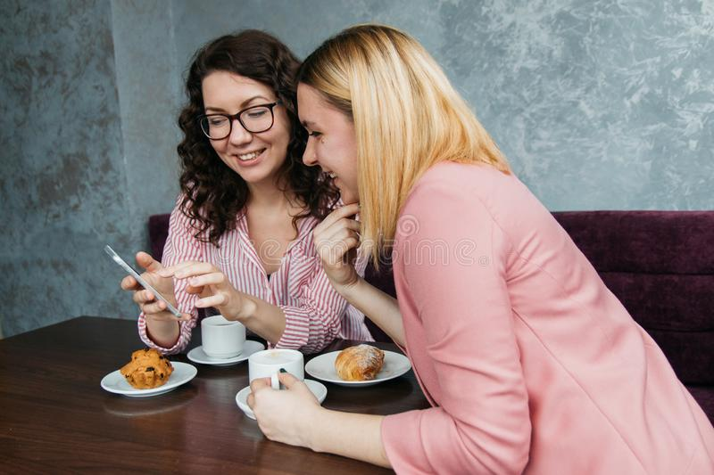 Two young attractive women friends are drinking coffee stock photography