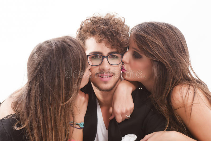 Two young attractive women kissing man stock photos