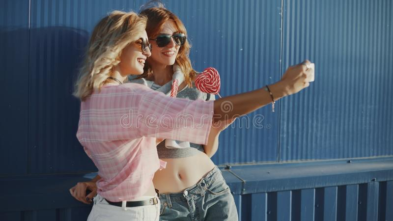 Beautiful young woman uses a smartphone on the street and licks colored lollipopTwo young attractive women in sun glasses talking, stock photography