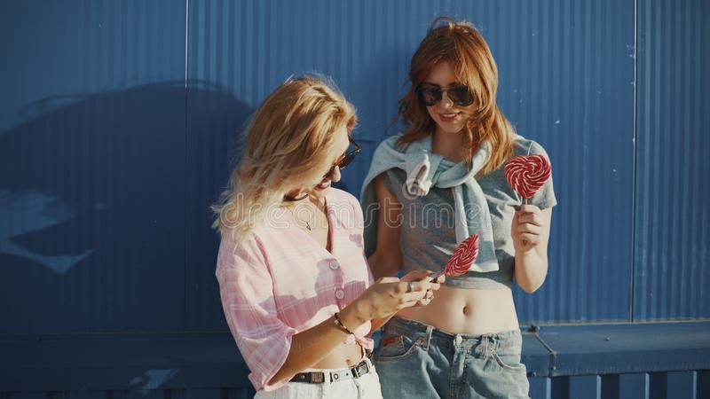 Beautiful young woman uses a smartphone on the street and licks colored lollipopTwo young attractive women in sun glasses talking, royalty free stock photo