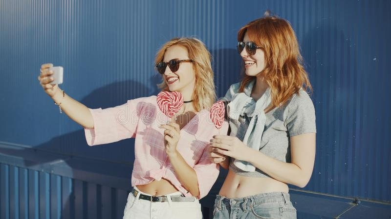 Beautiful young woman uses a smartphone on the street and licks colored lollipopTwo young attractive women in sun glasses talking, royalty free stock image
