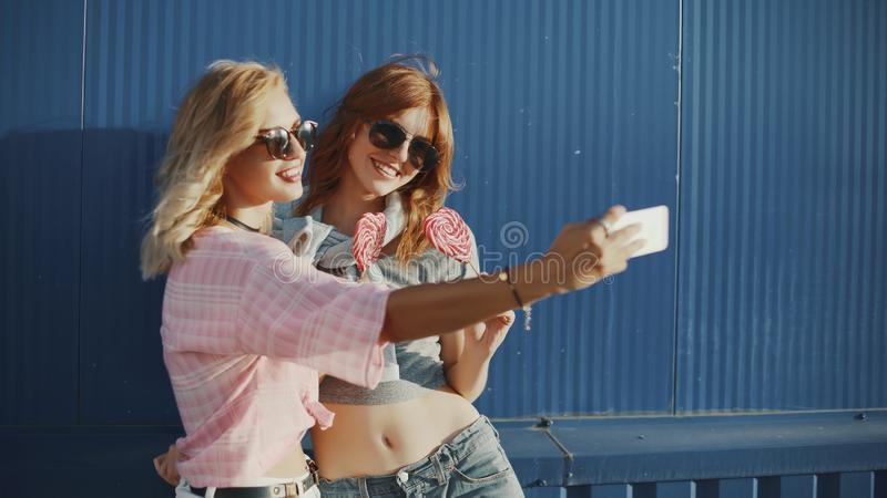 Beautiful young woman uses a smartphone on the street and licks colored lollipopTwo young attractive women in sun glasses talking, royalty free stock images