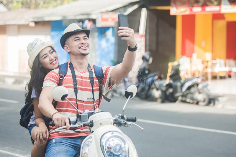 Two young backpackers taking selfies using mobilephones camera w. Portrait of two young backpackers taking selfies using mobilephones camera while on motorbike royalty free stock images