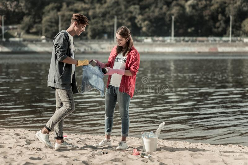 Two young beaming students standing near the river while cleaning the sand royalty free stock photography