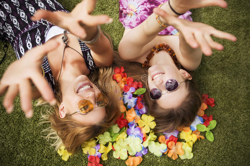 Two young beautiful blonde hipster girls on summer day having fun in european city. Green grass on a background and flower leafs. royalty free stock image