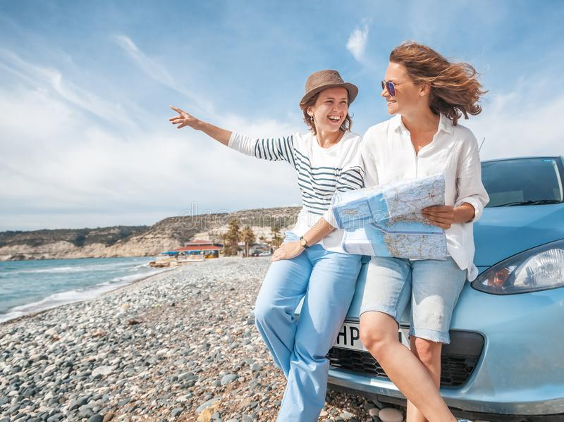 Two young beautiful female friends travel together by car, look royalty free stock images