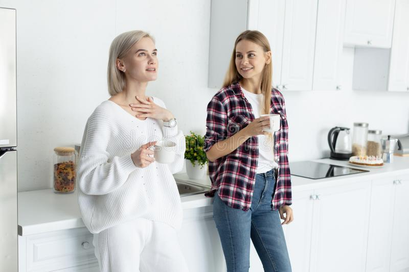 Two young beautiful females in casual clothes spending time together in the kitchen royalty free stock photography