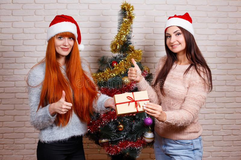 Two young beautiful friends in Santa caps with a gift box showin stock image