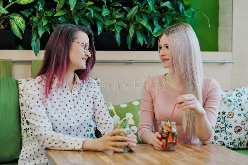 Two young beautiful girls, a blonde in a pink dress and a brunette with dyed hair, sit at a cafe table, drink lemonade stock photos