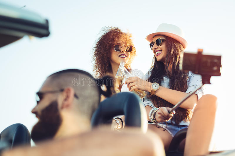 Two young beautiful girls are doing a photo of yourself in a convertible royalty free stock image