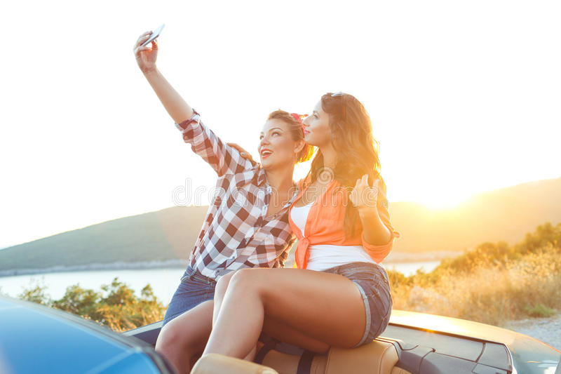 Two young beautiful girls are doing selfie in a convertible royalty free stock photos