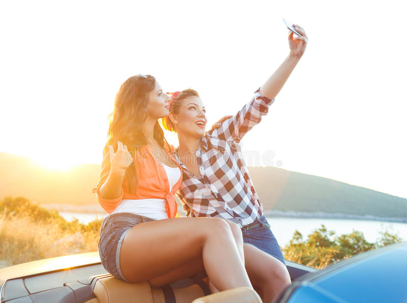 Two young beautiful girls are doing selfie in a convertible stock photo