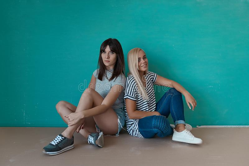 Two hipster girls posing in studio royalty free stock images