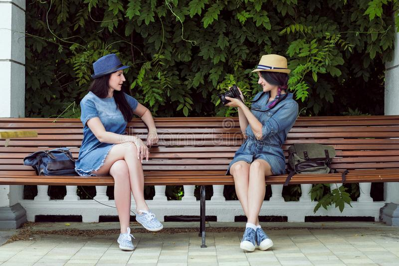 Two young beautiful girls in jeans dresses and hats sit on a bench in the park on a background of green plant walls, and stock images