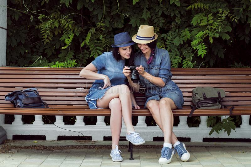 Two young beautiful girls in jeans dresses and hats sit on a bench in the park on a background of green plant walls, and royalty free stock image