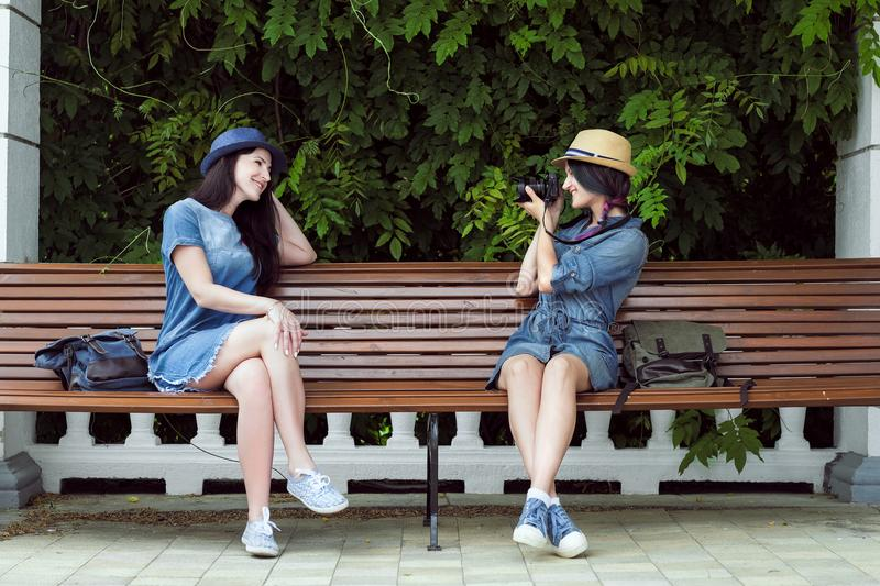 Two young beautiful girls in jeans dresses and hats sit on a bench in the park on a background of green plant walls, and royalty free stock photo