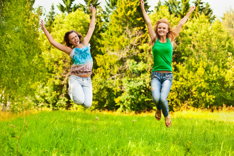 Two young beautiful girls jumps up stock images