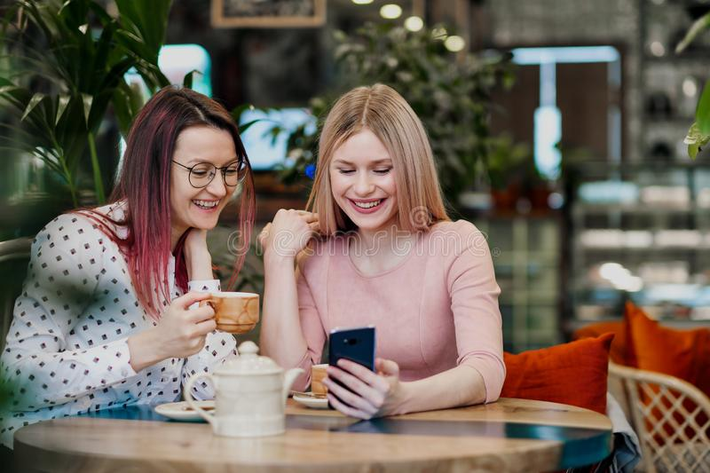 Two young beautiful girls sit in a green cafe at a table. Drink tea with croissants, chatting, laughing and taking royalty free stock photography