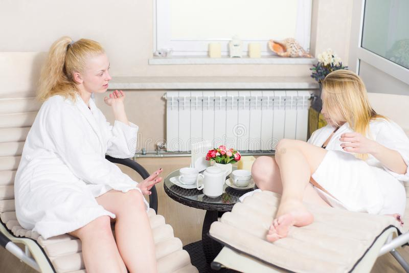 Two young beautiful girls in spa salon. blonde women are cute talking and drinking tea and coffee royalty free stock photos