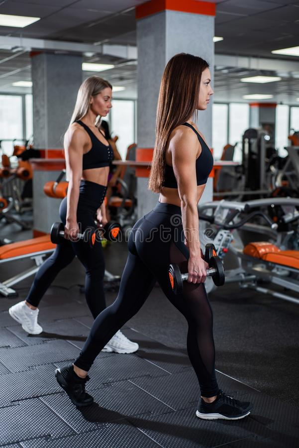 Two young, beautiful girls train legs and ass. Perform lunges forward with dumbbells. gym. Two young, beautiful girls train legs and ass. Perform lunges forward royalty free stock photo