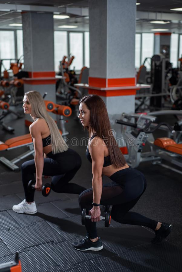 Two young, beautiful girls train legs and ass. Perform lunges forward with dumbbells. gym. Two young, beautiful girls train legs and ass. Perform lunges forward stock photography