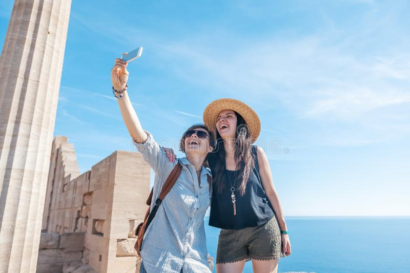 Two young beautiful happy woman female travel girlfriends doing royalty free stock photography