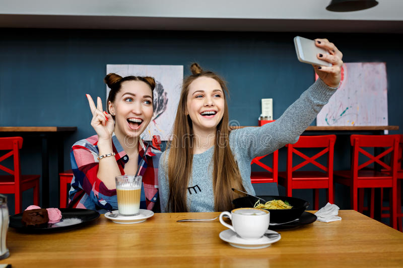 Two young beautiful hipster women sitting at cafe, stylish trendy outfit, europe vacation, street style, happy, having stock photos