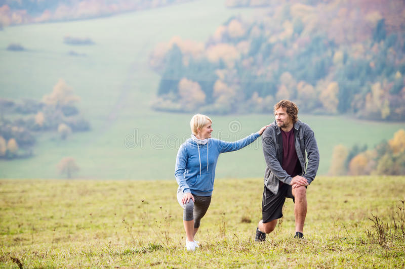 Two young beautiful runners in autumn nature, stretching legs stock image