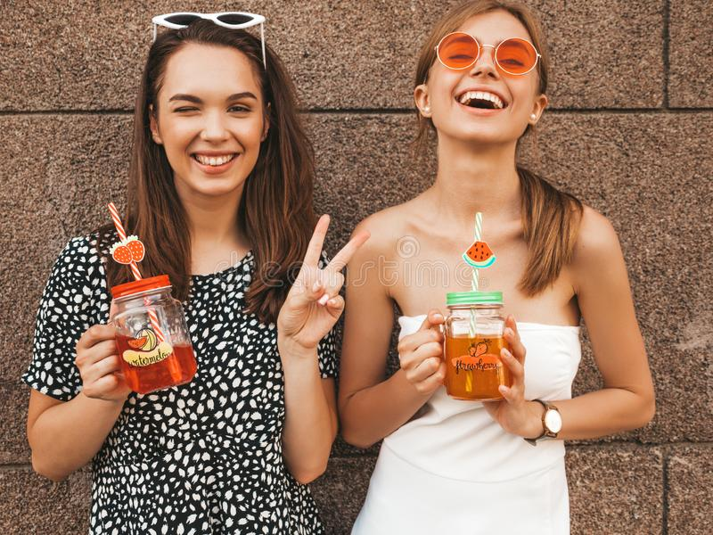 Two young beautiful smiling hipster girls in trendy summer clothes royalty free stock images