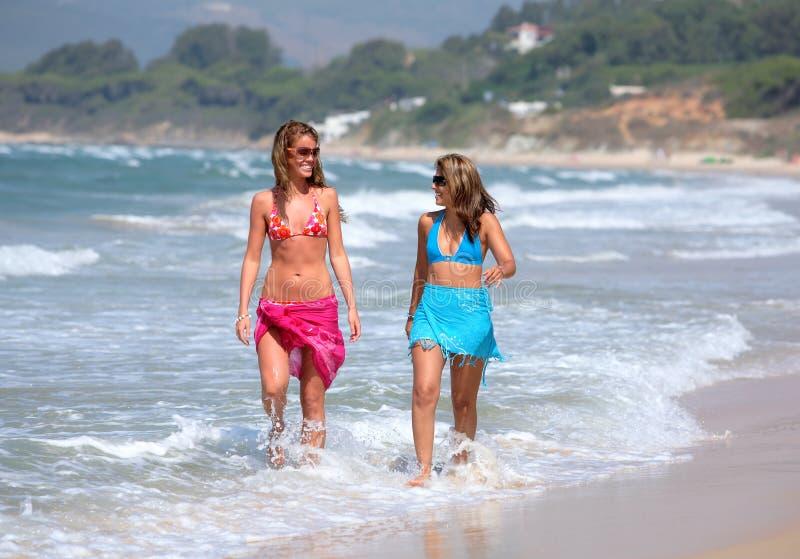 Two young beautiful tanned women walking along sandy beach stock photos