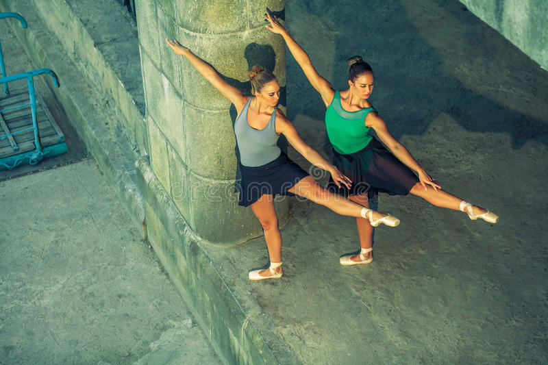 Two young beautiful twin sister dancing ballet in the city with ballet costume. urban sync dance. industrial street dancing. with stock photo