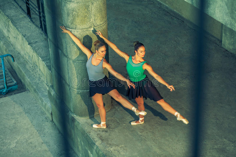 Two young beautiful twin sister dancing ballet in the city with ballet costume. urban sync dance. industrial street dancing. with royalty free stock photos