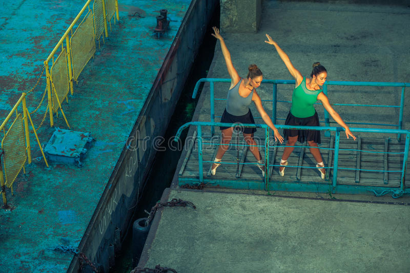 Two young beautiful twin sister dancing ballet in the city with ballet costume. urban sync dance. industrial street dancing. with royalty free stock image