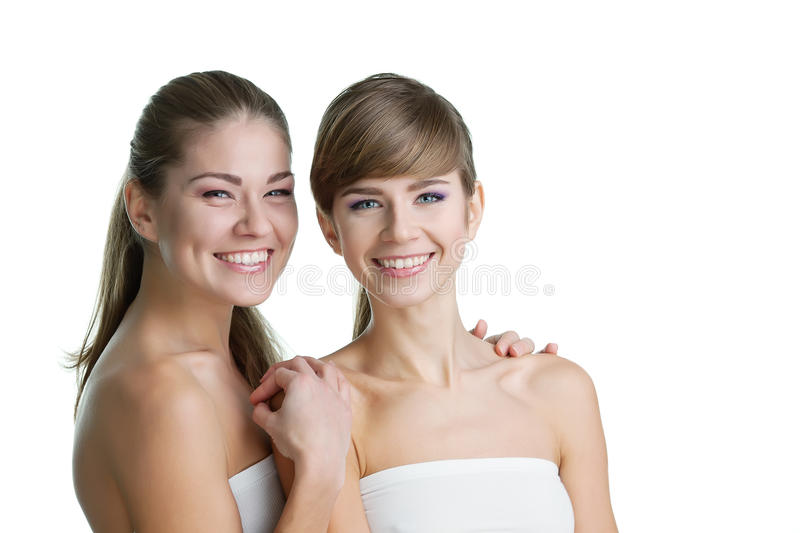 Two young beautiful women. Portrait of two young beautiful women on white background smilin stock image