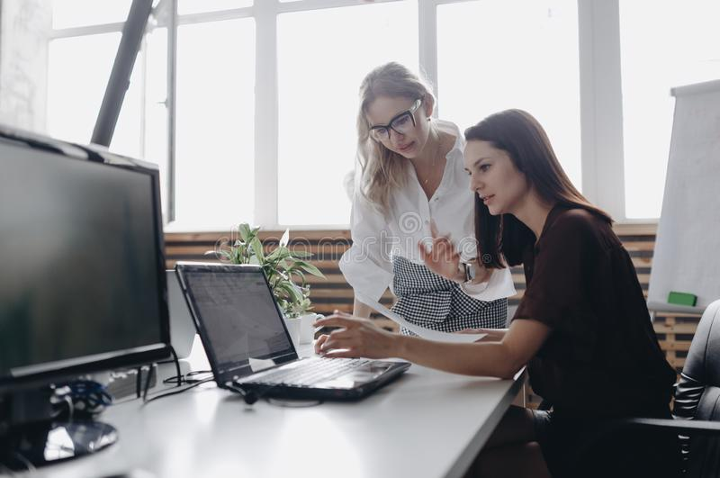 Two young beautiful women dressed according to office dreskod are working together with laptop at the desk in a light royalty free stock image