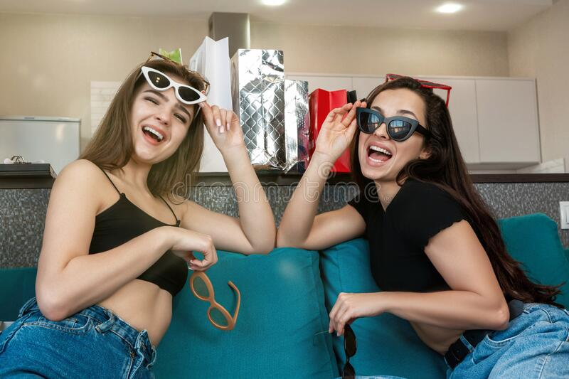 Two young beautiful women friends unpacking their goods after successful shopping, trying on sunglasses , shopaholic behaviour.  stock image