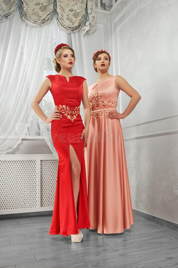 Two young, beautiful women in long, evening red and peach dresse stock image
