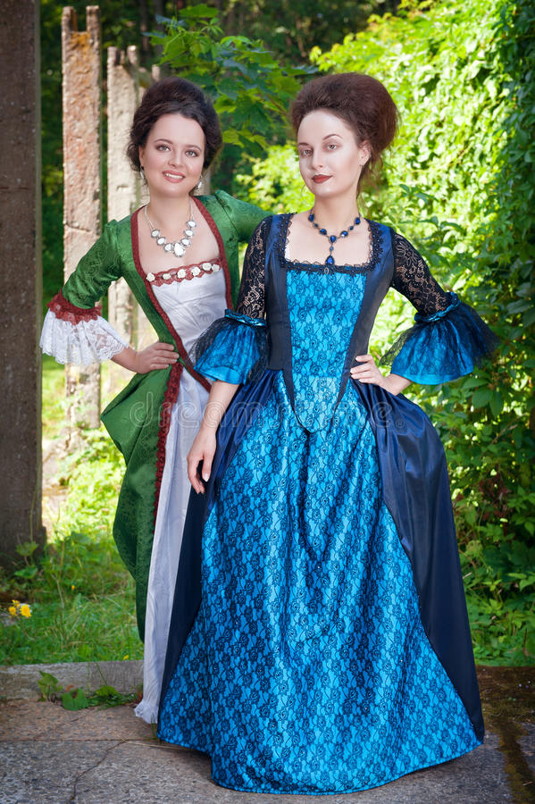Two young beautiful women in medieval dresses outdoor. Two young beautiful women in long medieval dresses outdoor royalty free stock photos