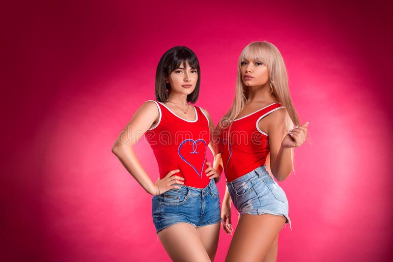 Two young beautiful women posing in Studio in shorts, fitness stock photos